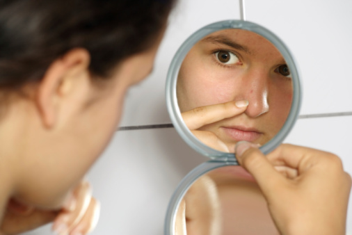 Photo of young woman looking into a mirror