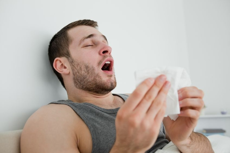 Photo of a man having a sneezing fit
