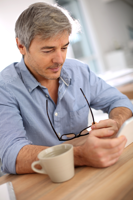 Photo of a man reading something on a tablet device