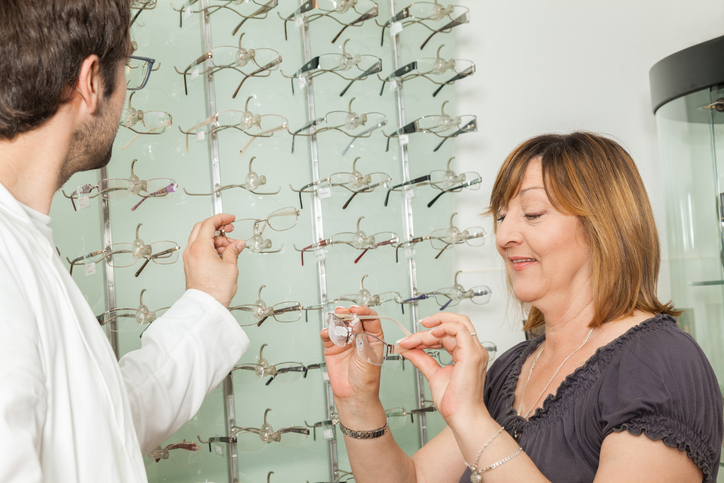 Photo of a woman looking at glasses with an optician