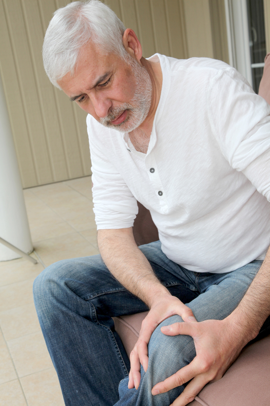 Photo of man holding his knee in pain