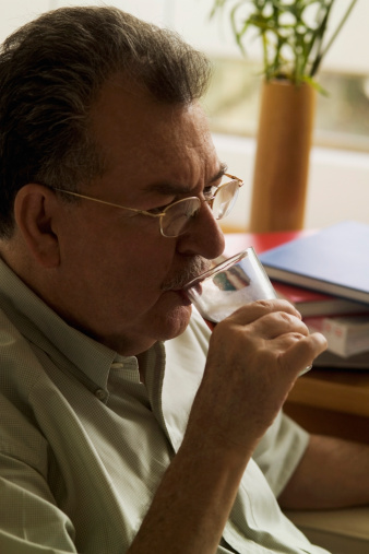 Photo of an older man drinking from a glass