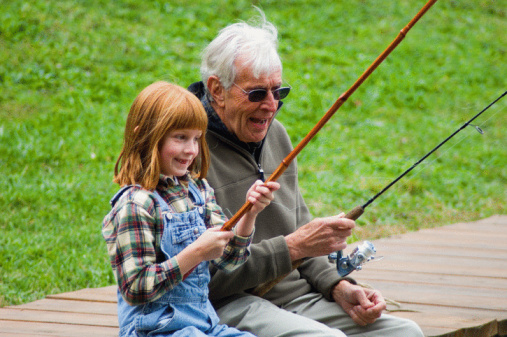 Photo of an elderly man fishing with his granddaughter