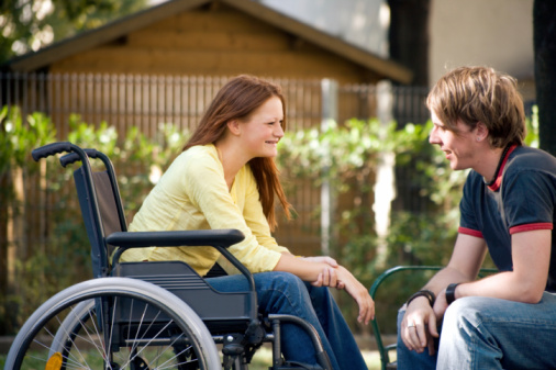 Photo of a young woman in a wheelchair talking to a friend