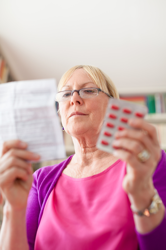 Photo of a woman reading a package insert