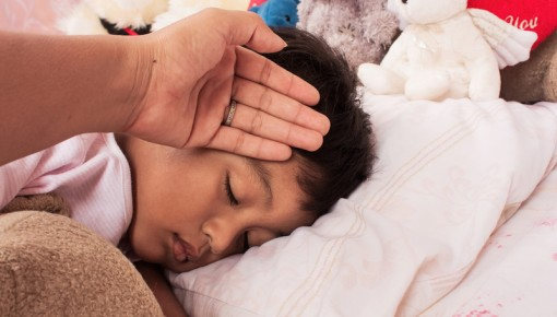 Photo of an adult's hand against a sleeping child's forehead