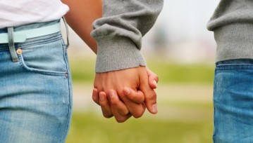 Photo of young couple holding hands