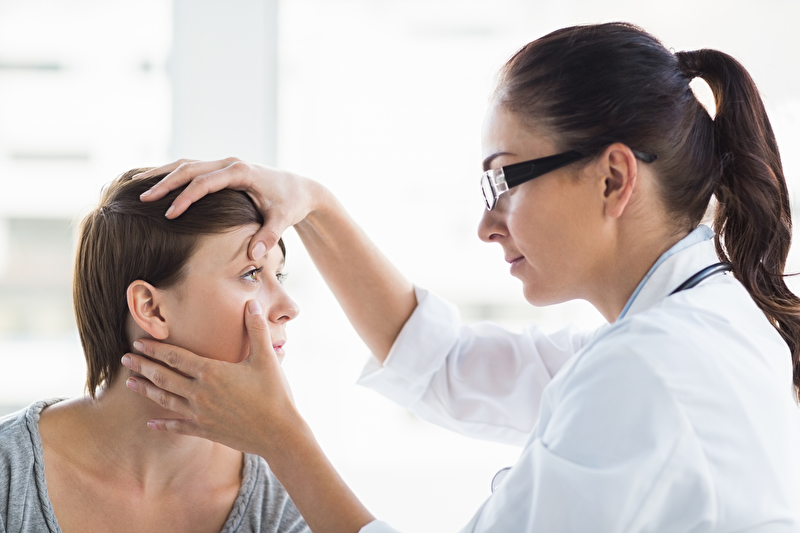 Photo of a doctor examining a woman's eye