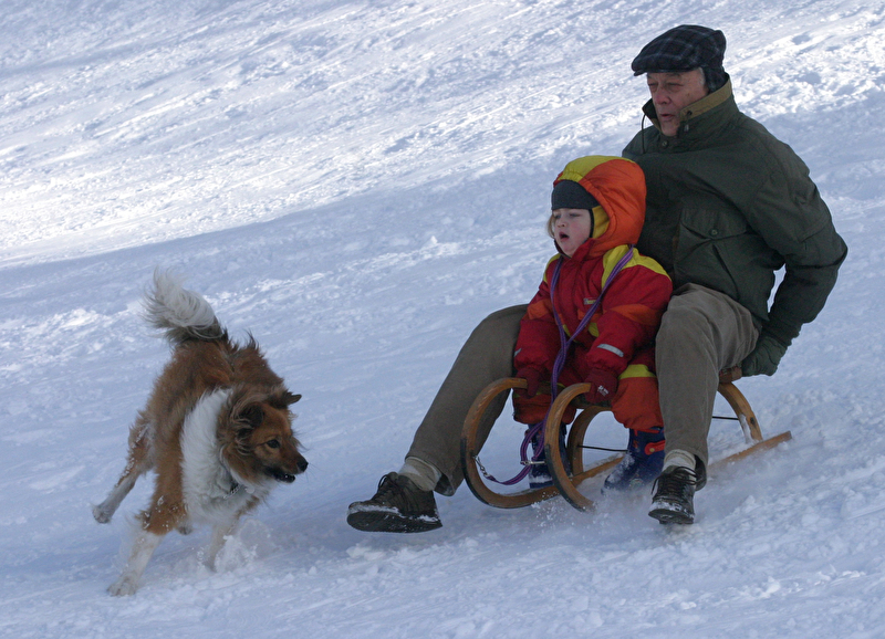 photo of a grandfather and grandchild playing in the snow