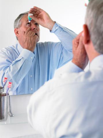 Photo of a man using eye drops