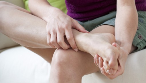 Photo of a woman holding her foot in pain