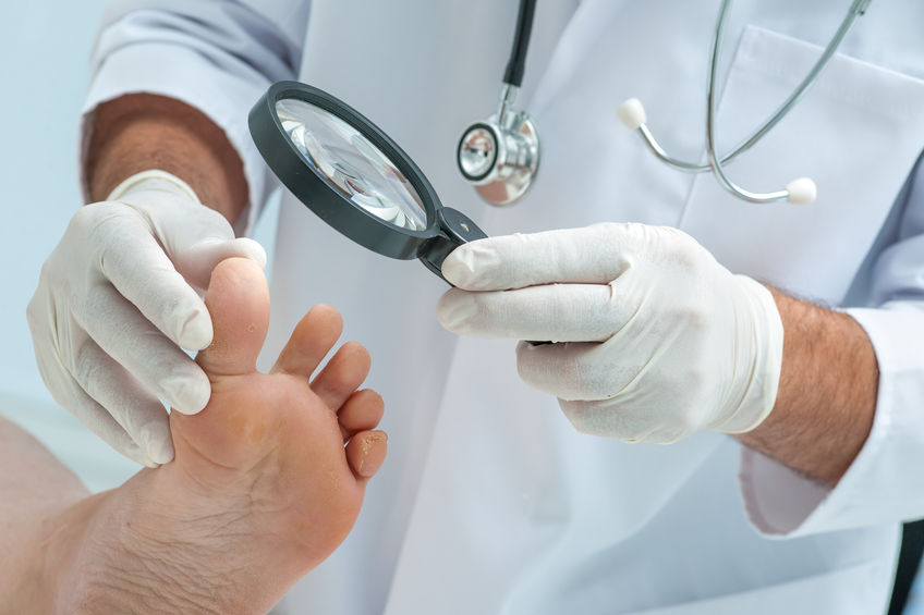 Photo of a doctor inspecting someone's toes for abnormalities