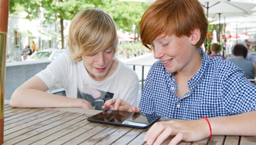 Photo of two teenagers using a tablet device outside on a sunny day