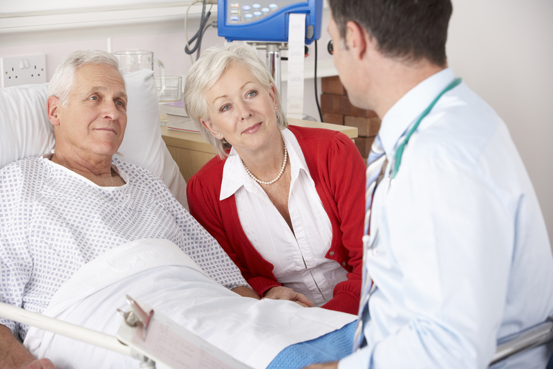 Photo of an older man in a hospital bed talking to a doctor