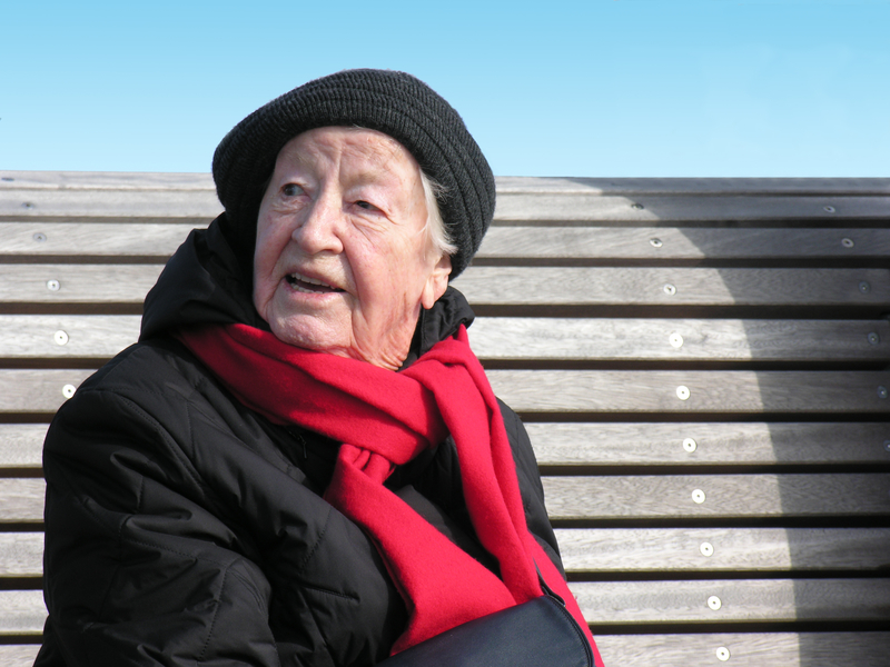 Photo of an elderly woman sitting on a bench