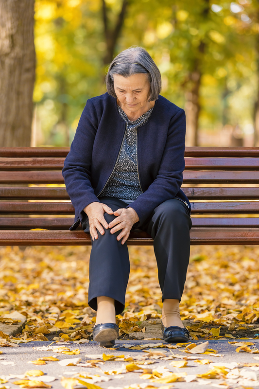 Photo of a woman with knee pain sitting on a bench