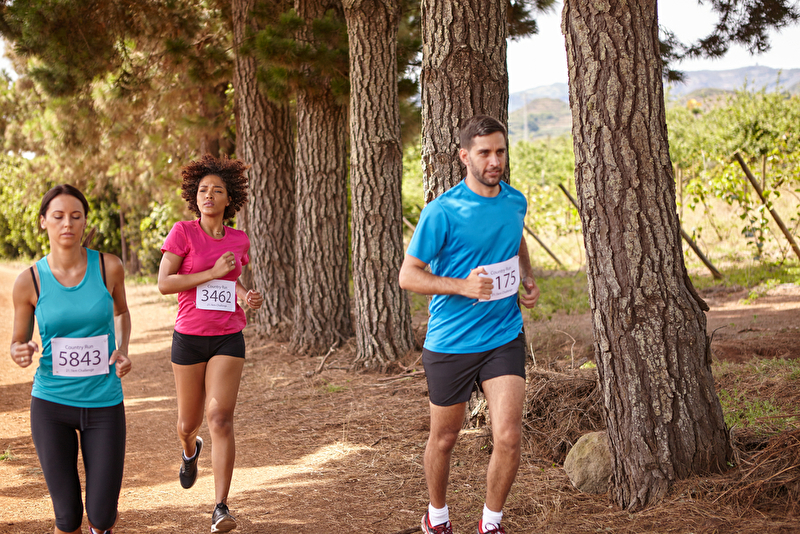 Photo of three people running outdoors