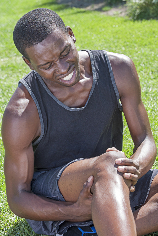 Photo of an athletic man holding his knee in pain