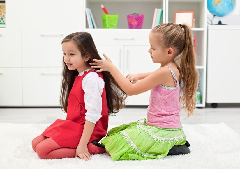 Photo of two girls playing with each other's hair