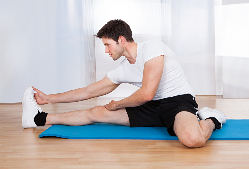 Photo of a man doing stretching exercises
