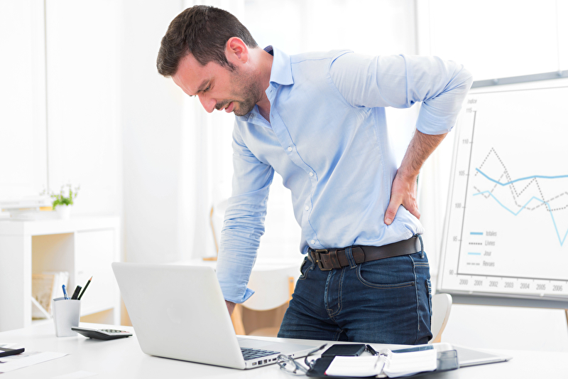 Photo of a man with back pain at a desk