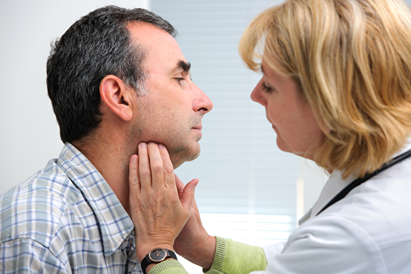 Photo of a doctor examining a patient's throat