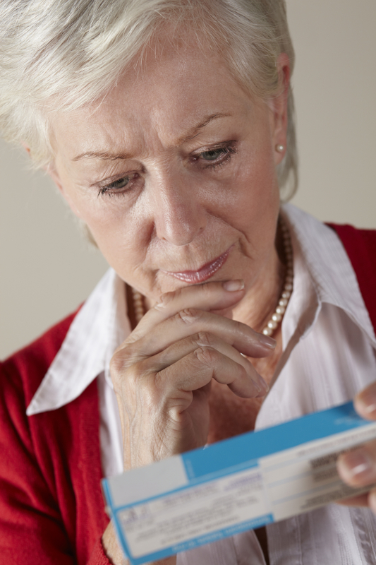Photo of a woman reading the print on a drug package