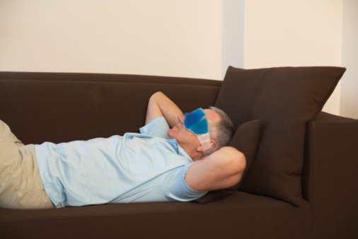 Photo of man with a migraine on a sofa