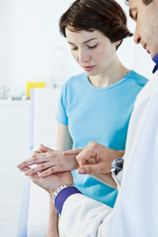 Photo of a young woman being examined by a dermatologist