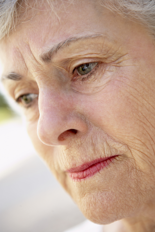 Photo of an elderly woman lost in thought
