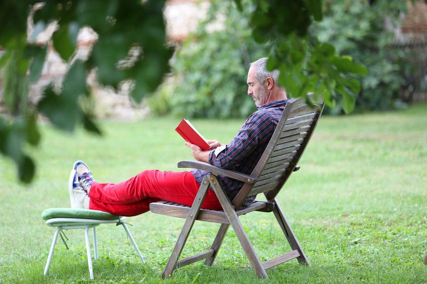 Photo of man reading in garden
