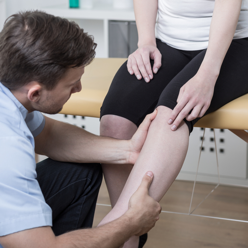 Photo of a physiotherapist examining a patient's leg