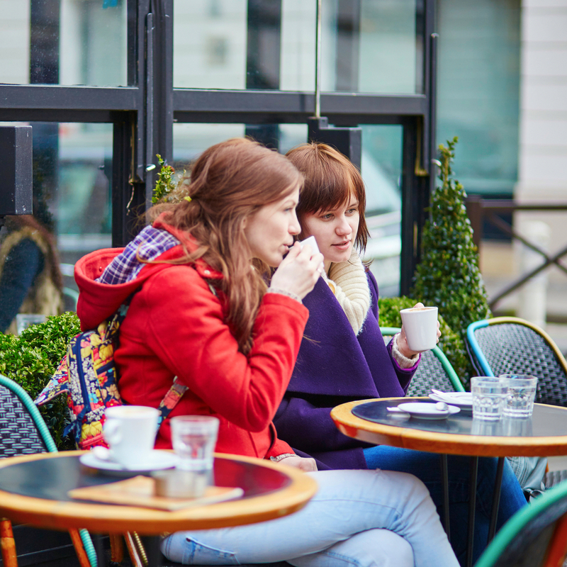 Photo of two women sitting outside a café