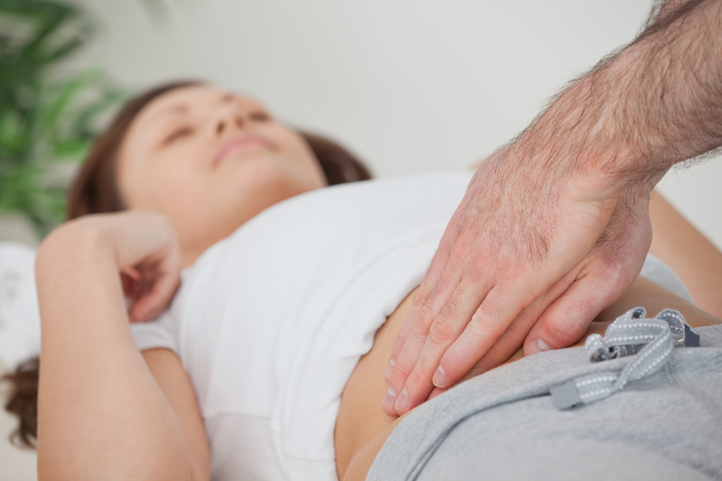 Photo of a doctor feeling a patient's abdomen