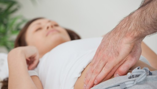 Photo of a doctor feeling a patient's belly