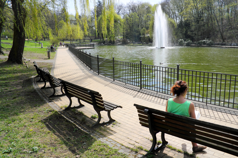 Photo of a woman sitting near a pond