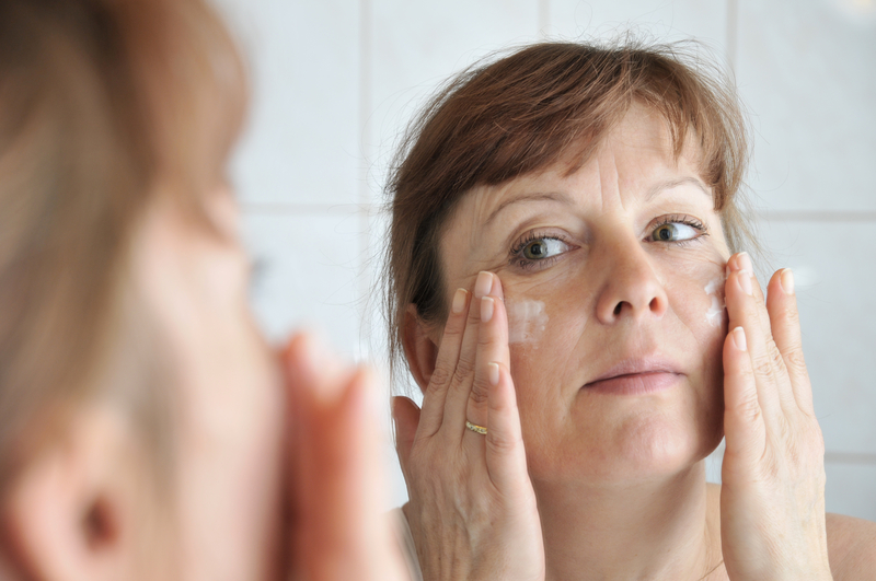 Photo of a woman applying cream to her face