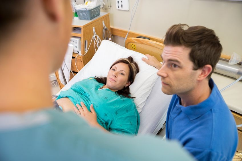 Photo of a pregnant woman and her partner talking to doctor in hospital