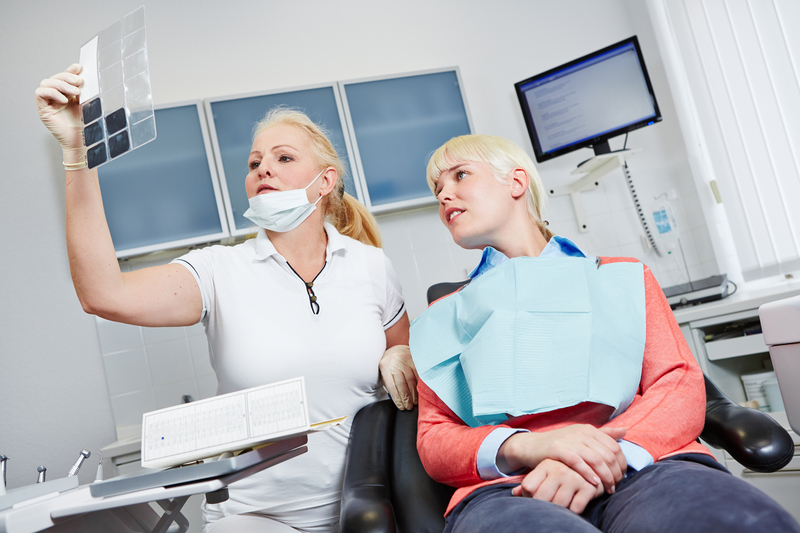 Photo of a dentist discussing an x-ray with a patient